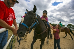 Thirteen-year-old Emily Lunning of Mason City, right, lifts up her five-year-old friend Madeline Cornish onto her pony Shadow as fair board member Randy Thomas holds the reins Saturday at the North Iowa Fair in Mason City. Lunning and Shadow will compete in the Garner Saddle Club Fun Horse Show today at the fair.
